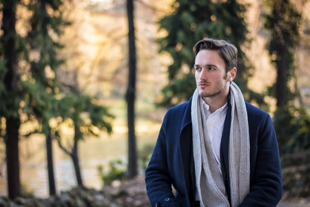 winter clothes: Handsome young man outdoor in winter fashion, wearing black coat and woolen scarf in city park Stock Photo