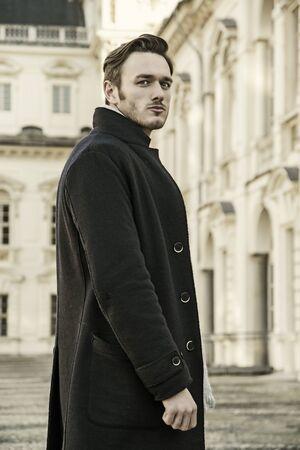 chaqueta: Apuesto hombre de moda llevar oscura al aire libre la chaqueta de pie en un entorno de ciudad europea con un elegante edificio histórico detrás de él