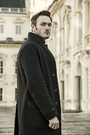 serious man: Handsome trendy man wearing dark coat standing outdoor in European city setting with elegant old historic building behind him Stock Photo