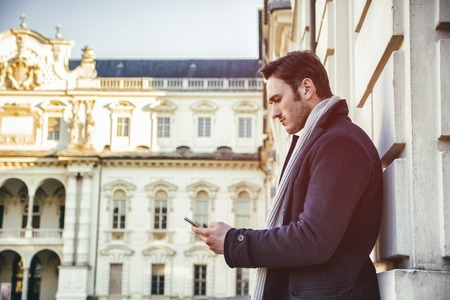 Handsome trendy man wearing dark coat standing and looking down at a cell phone that he is holding, outdoor in European city setting with elegant old historic building behind Stock Photo