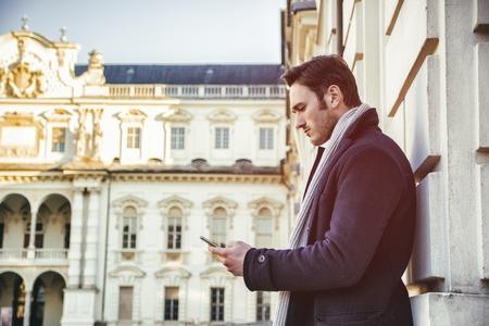 uomini belli: Uomo bello alla moda indossando cappotto scuro in piedi e guardando un telefono cellulare che ha in mano, all'aperto in ambiente città europea con elegante edificio storico dietro