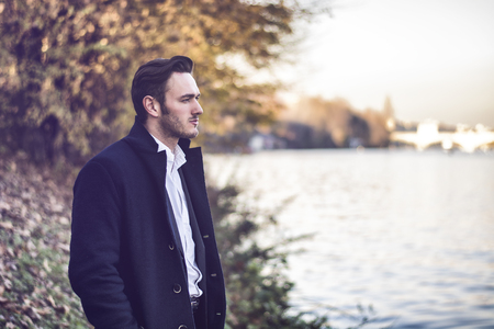 hunk: Handsome young man outdoor in winter fashion, wearing black coat and woolen scarf next to lake or river