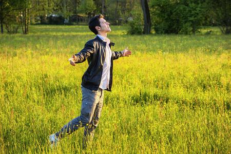 persona respirando: Hombre joven que celebra la naturaleza de pie en el prado con los brazos extendidos al sol en el campo