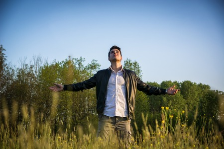 Young man celebrating nature standing in grassland with outstretched arms in the sunshine at countryside
