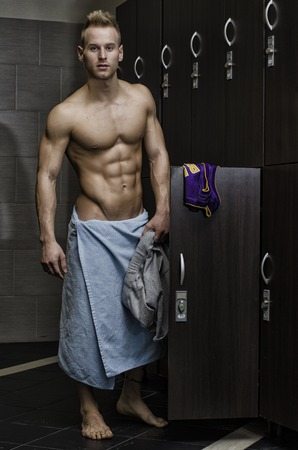 gym room: Shirtless muscular young male athlete in gym dressing room, smiling with towel around waist