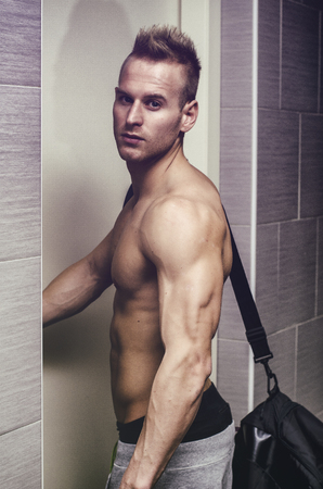 shot from behind: Shirtless muscular young man opening door, with gym bag on shoulder, shot from behind