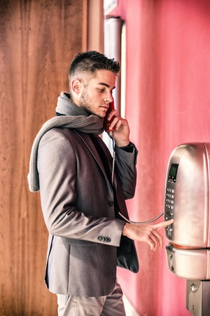 pay phone: Handsome stylish young man in a tailored jacket and scarf standing using a pay phone waiting for a connection, profile view
