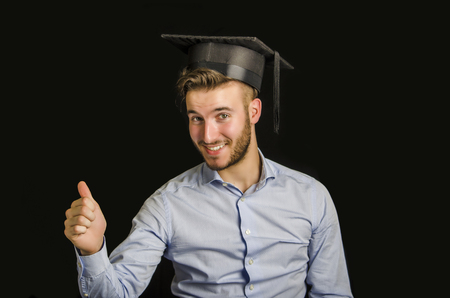 Happy young man graduating from college, with graduation hat, doing thumb up sign