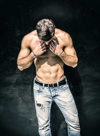 Handsome bearded shirtless young man standing against black wall, looking down at himself Фото со стока