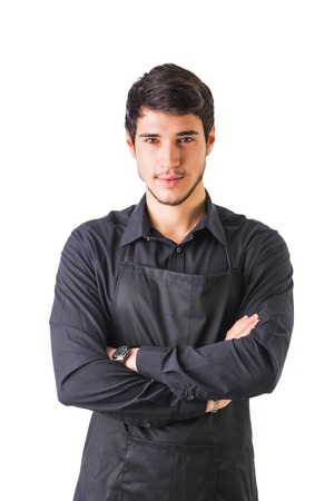 waiter: Young chef or waiter posing, wearing black apron and shirt isolated on white background, with arms crossed on his chest