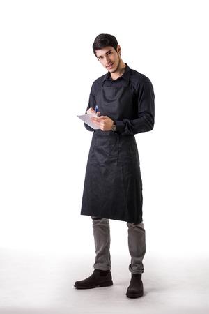 mandil: Tiro integral de joven chef o posando camarero, vestido con delantal negro y la camisa, para escribir en el bloc de notas, aislado en fondo blanco