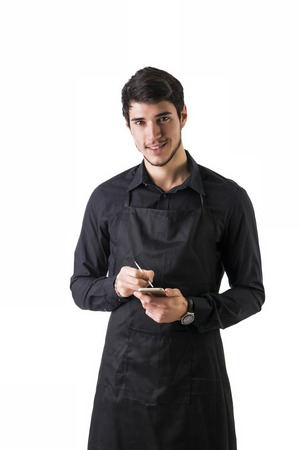 mandil: Tiro integral de joven chef o posando camarero, vestido con delantal negro y camisa, escribir dispositivo electr�nico fin, aislado en fondo blanco
