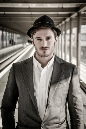dapper: Head and Shoulders Portrait of Stylist Young Man Wearing Suit and Hat Looking at Camera While Standing on Moving Sidewalk in Building