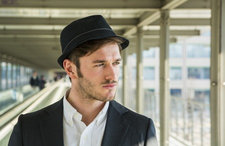 black head and moustache: Head and Shoulders Portrait of Stylist Young Man Wearing Suit and Hat Looking to the Side Out Window While Standing on Moving Sidewalk in Building Stock Photo