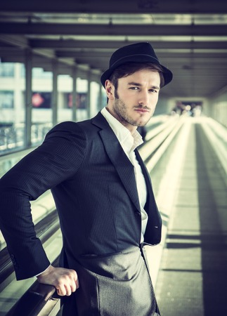 black head and moustache: Head and Shoulders Portrait of Stylist Young Man Wearing Suit and Hat Looking at Camera While Standing on Moving Sidewalk in Building