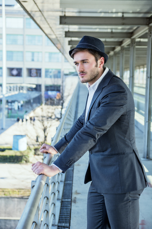 dapper: Head and Shoulders Portrait of Stylist Young Man Wearing Suit and Hat Looking to the Side Out Window While Standing on Moving Sidewalk in Building Stock Photo