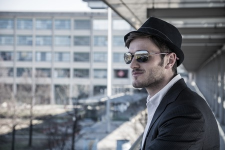 preoccupied: Head and Shoulders Portrait of Stylist Young Man Wearing Suit and Hat Looking to the Side Out Window While Standing on Moving Sidewalk in Building Stock Photo