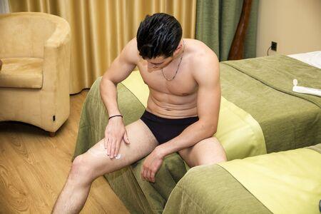 beine spreizen: Junger Mann, die Anwendung Bodylotion, seine Beine, Blick nach unten.