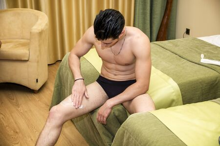 Young man applying body lotion to his legs, looking down. Stock Photo