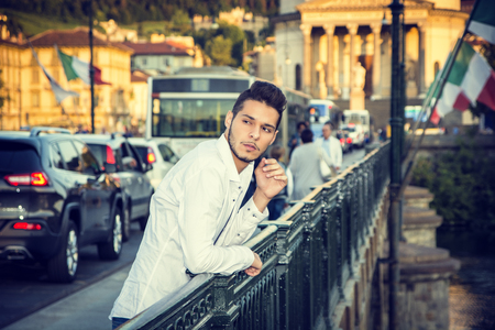 city traffic: Handsome Young Man Leaning Against Metal Handrail at the River in European City, with Cars Behind Him. Turin, Italy Stock Photo