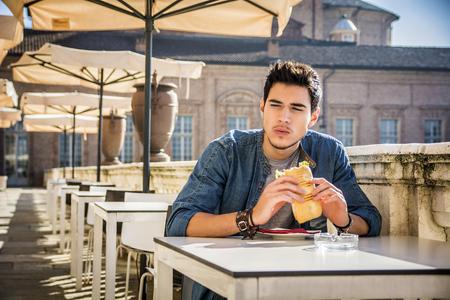 Hombre joven que sostiene sándwich mientras está sentado en el café, mirando a un lado serio. Verano Foto de archivo