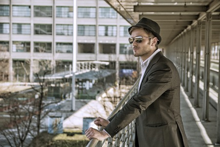 suave: Head and Shoulders Portrait of Stylist Young Man Wearing Suit and Hat Looking to the Side Out Window While Standing on Moving Sidewalk in Building Stock Photo