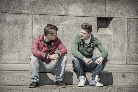 men talking: Two young men talking while sitting on curb. Stock Photo