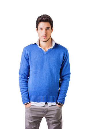 Smiling cool young man with wool sweater on white background looking at camera