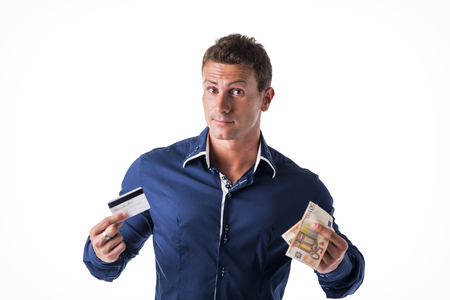 means: Young man holding banknotes and credit card, choosing between the two means of payment. Isolated, studio shot