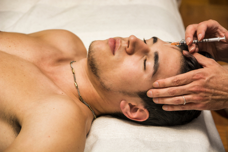 Close-up of young man getting injection of botox on forehead, laying down with eyes closed