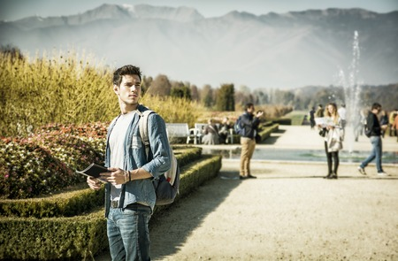 alongside: Handsome young man wearing a backpack sightseeing in a lush green autumn park, standing alongside a canal with swans holding a map or brochure, looking into the distance as though lost Stock Photo