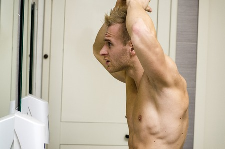 beautycare: Shirtless, muscular young man, towel around waist, looking at his hair in bathroom mirror