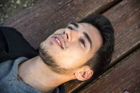 horizontal haircut: Close-up of young man relaxing on bench and looking up, smiling
