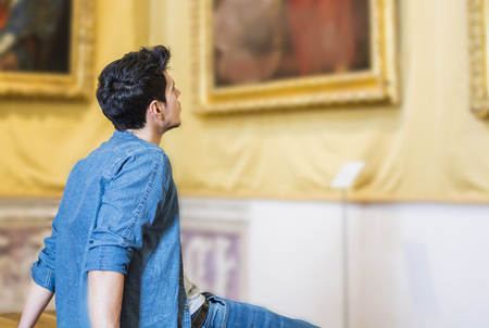 Half Body Shot of a Thoughtful Handsome Young Man, Looking At Painting Sitting on Bench Inside a Museum