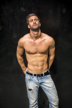ハンサムなのひげを剃っていない上半身裸若い男黒の壁に立って、カメラ目線