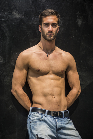 young unshaven: Handsome unshaven shirtless young man standing against black wall, looking at camera