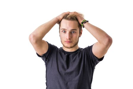 puzzlement: Young bearded man with hands on head looks puzzled. Isolated, white background. Stock Photo