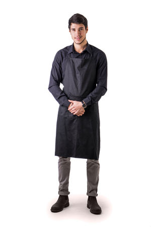 mandil: Joven chef o posando camarero, vestido con delantal negro y la camisa aislados sobre fondo blanco