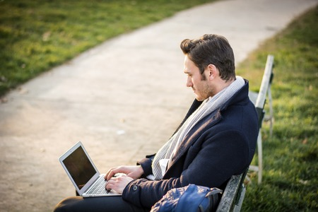 businessman working at his computer: Handsome elegant businessman sitting on a wooden bench working outdoors in an urban park typing information onto his laptop computer with a serious expression Stock Photo