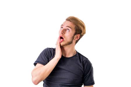 an open mouth: joven agotado mirando hacia arriba con la boca abierta. estudio de disparo. Foto de archivo