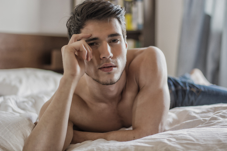 modelos desnudas: Sexy modelo masculino descamisado que miente solamente en su cama en su dormitorio, mirando a la cámara con una actitud seductora