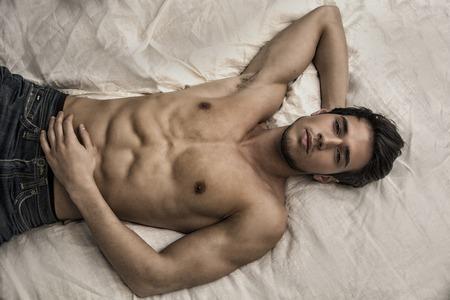 seins nus: Mod�le sexy masculin Torse nu couch� seul sur son lit dans sa chambre, regardant la cam�ra avec une attitude s�duisante