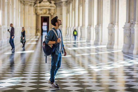 guia turistico: Foto de cuerpo entero de un hombre joven hermoso pensativo, Llevar un Guía, Mirar hacia dentro de un museo