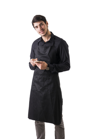 handheld device: Young chef or waiter posing, wearing black apron and shirt isolated on white background, taking order writing on handheld device Stock Photo