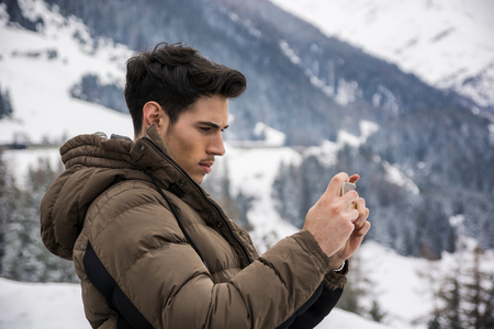outerwear: Side view on dark haired young man in outerwear taking photo of landscape in mountain with smartphone