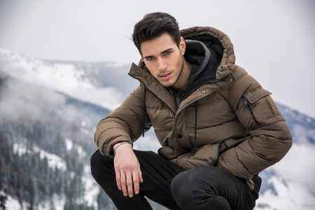 outerwear: Handsome man in outerwear sitting while looking at camera. Snowy landscape on background