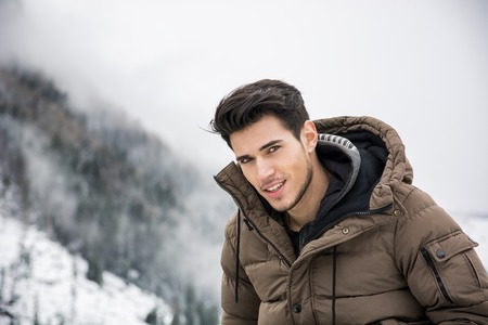 outerwear: Handsome man in outerwear sitting while looking at camera smiling. Snowy landscape on background