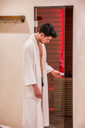towelling: Handsome young man in white bathrobe entering or exiting sauna, opening glass door to get in or out
