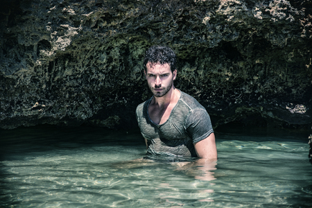 Attractive young athletic man in the sea or ocean by the rocky shore, wearing wet t-shirt, serious expression Stock Photo