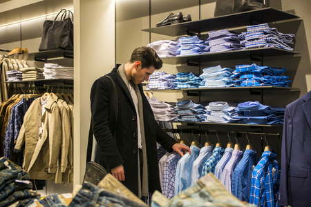 menswear: Side view of young male customer choosing shirt in menswear shop